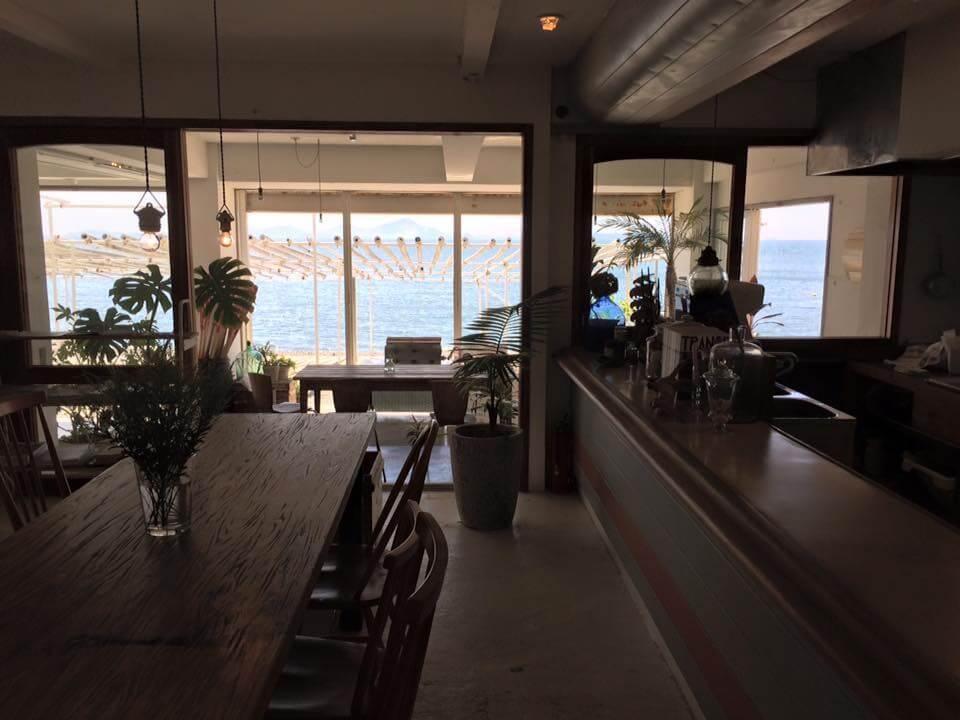 カフェの店内の木陰は気持ちいい風が吹き青い海が広がっています